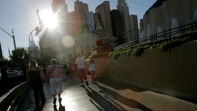 Tourists walk in harsh afternoon sunlight in Las Vegas, on July 3 , 2007. Las Vegas has the nation's most intense urban heat island effect.