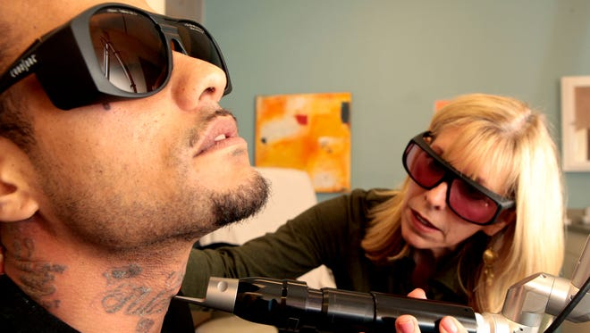 Leroy Turner receives laser treatment on his tattoos from physician assistant Karen Whitney at Advanced Cosmetic Surgery & Laser Center in Norwood.