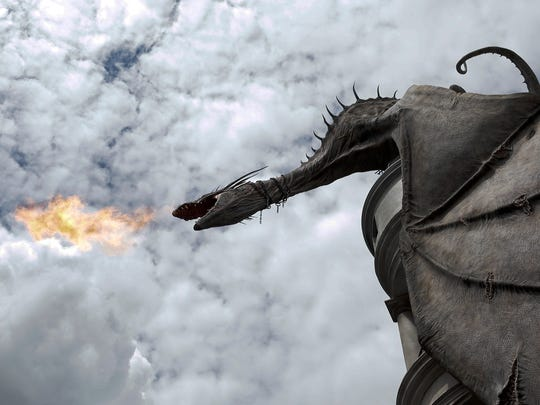 A dragon breathes fire from atop Gringnotts Bank during a preview of Diagon Alley at the Wizarding World of Harry Potter at Universal Orlando, Thursday, June 19, 2014, in Orlando, Fla.