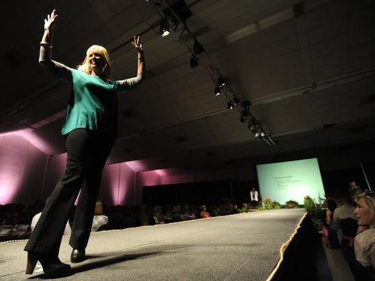 Thomas Metthe/Reporter-News   Stacey Sanford waves to the crowd as she walks the runway during the 10th Anniversary Fashions for the Cure event benefiting Cancer Services Network on Tuesday, Oct. 1, 2013, at the Abilene Civic Center.