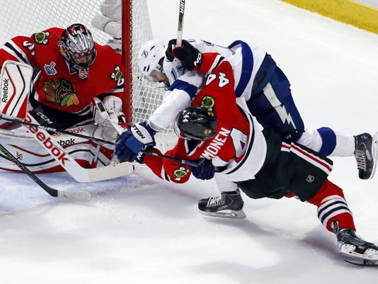 Chicago Blackhawks' Kimmo Timonen, front right, and Tampa Bay Lightning's Alex Killorn get tangled up as Blackhawks goalie Corey Crawford, left, watches during the first period of Wednesday's Game 4 of the Stanley Cup Finals in Chicago.