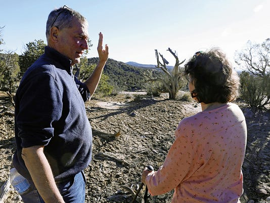Scott and Susan Ramsey discuss the possible path of an alleged flying saucer Friday at Hart Canyon in Aztec.