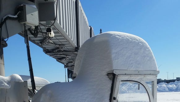 Nearly 30 inches of snow sits at a Delta Air Lines