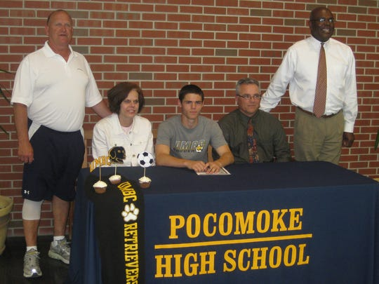 Jordan Becker, center, signs his letter of intent to