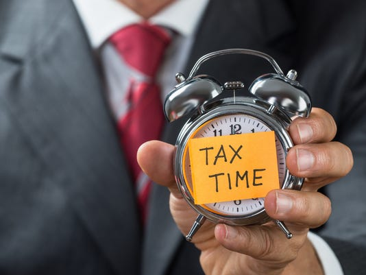 Businessman Holding Alarm Clock With Tax Time Note