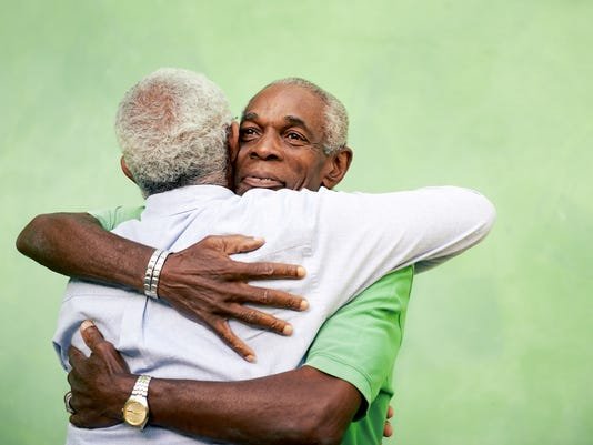 Old friends, two senior african american men meeting and hugging