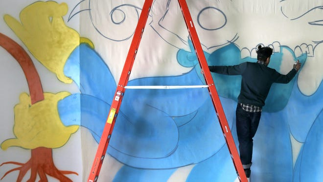 New York street artist Nepo (Juan Roman Lopez) works on a wall-size piece at the University of Wisconsin-Fox Valley's Aylward Gallery in Menasha. The exhibit of his work runs through March 5.