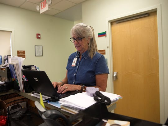 Carol Ewing, a certified nurse midwife works on her