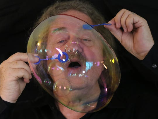 "Tom McAllister blows a ""galaxy"" bubble, in which smaller"