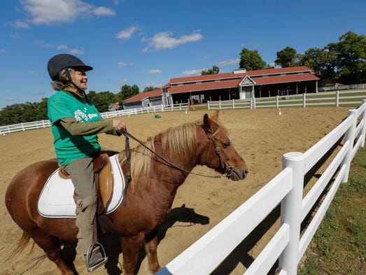 Melissa Nagel of Brighton and instructor rides Diamond around while giving the pony exercise at the Equestrian Center at the 990-acre Girl Scoout Camp Innisfree in Howell.