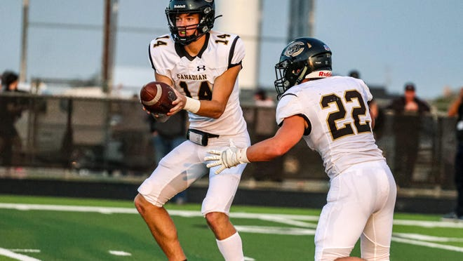 Canadian's Josh Culwell (14) takes the snap as running back Jake Krehbiel awaits a handoff during Friday night's game at Bushland. Canadian won 46-19.