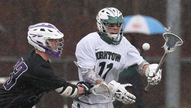 From left, John Jay's Danny Skluth (33) and Yorktown's Luke Palmadesso (11) battle for ball control during a boys lacrosse game at Yorktown High School March 29, 2014. Yorktown won the game 11-4.
