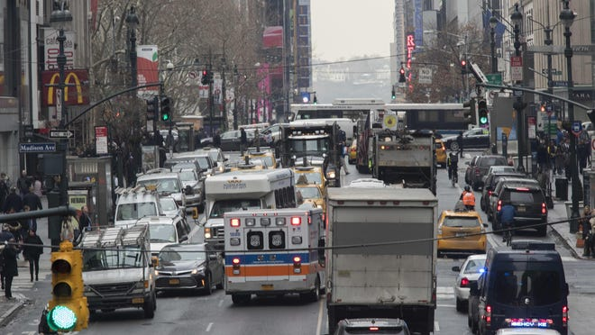 In this Jan. 11, 2018 photo, an ambulance is seen driving in the wrong lane to get around traffic on 42nd Street in New York. The idea is gaining momentum: Charging motorists an as-yet-undetermined toll – $11.52 according to past recommendations – to drive south of 61st Street in Manhattan.