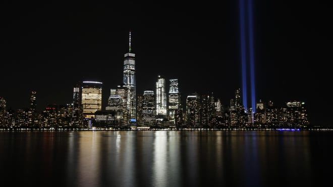 FILE - In this Sept. 11, 2017 file photo, the Tribute in Light illuminates in the sky above the Lower Manhattan area of New York, as seen from across the Hudson River in Jersey City, N.J. The coronavirus pandemic has reshaped how the U.S. is observing the anniversary of 9/11. The terror attacks' 19th anniversary will be marked Friday, Sept. 11, 2020, by dueling ceremonies at the Sept. 11 memorial plaza and a corner nearby in New York.
