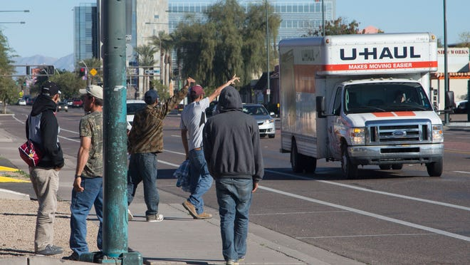 Day laborers outside a Circle K on Arizona Avenue in Chandler approach a U-Haul truck Wednesday, Feb. 11, 2015, to look for work.