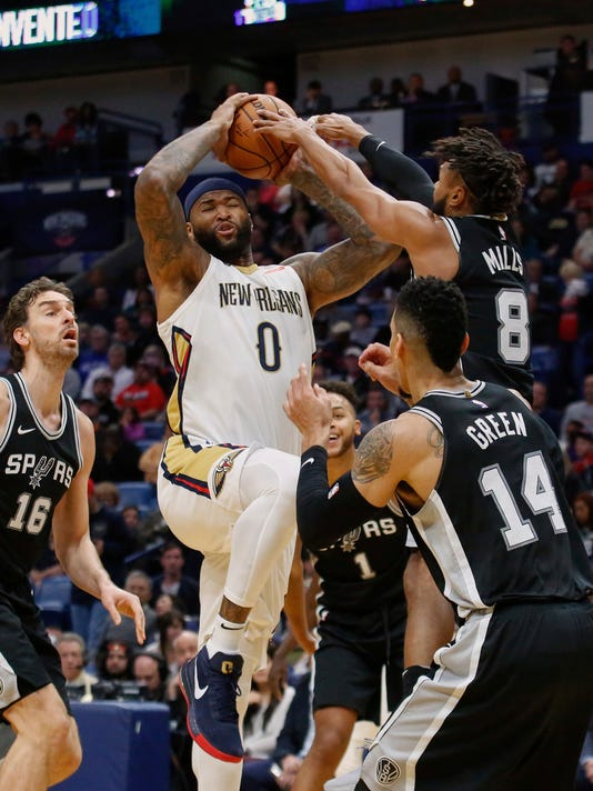 New Orleans Pelicans center DeMarcus Cousins (0) powers past San Antonio Spurs guard Patty Mills (8), guard Danny Green (14) and center Pau Gasol (16) for a dunk in the first half of an NBA basketball game in New Orleans, Wednesday, Nov. 22, 2017. (AP Photo/Scott Threlkeld)