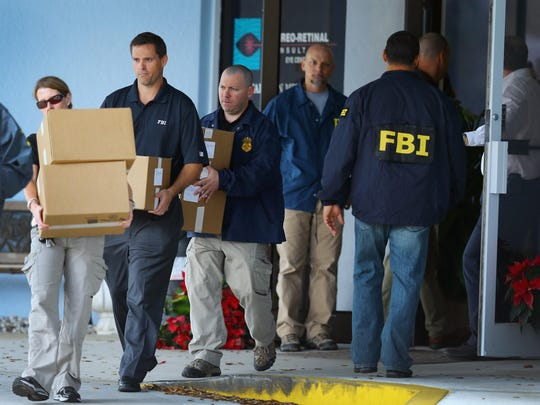 FBI agents carry out boxes as law enforcement officials investigate the medical-office complex of Dr. Salomon Melgen in Florida on Jan. 30, 2013.