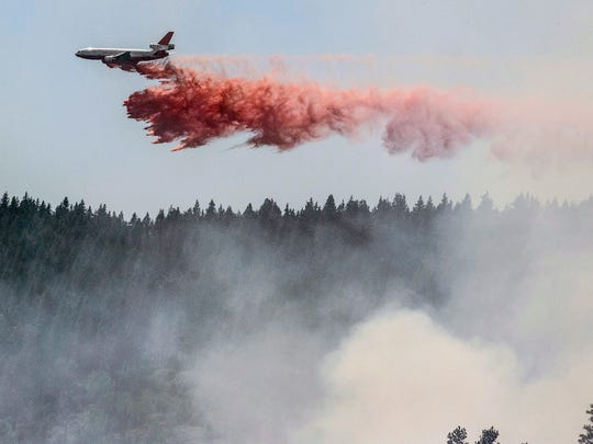 A plane drops fire retardant as firefighters battle a blaze in El Portal, Calif., near Yosemite National Park on Tuesday, July 29, 2014. Firefighters in the state are also battling another wildfire in the Sierra Nevada foothills east of Sacramento.