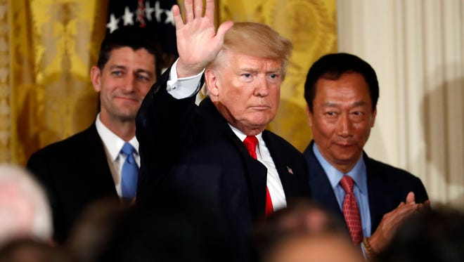 President Donald Trump waves after he announced last July that Foxconn planned to build a massive plant in Wisconsin. To the left is House Speaker Paul Ryan. To the right is Foxconn CEO Terry Gou.