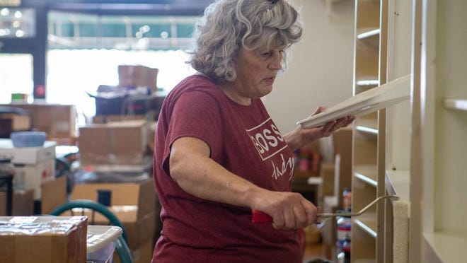 Kymm Ledbetter, owner of Prairie Glass Studio, paints a shelf Wednesday afternoon at her business' new location, 506 S.W. 10 Ave. Ledbetter plans for Prairie Glass to reopen at the new spot on Nov. 6.