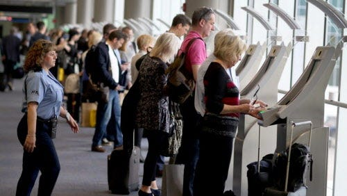 Passengers use the Automated Passport Control Kiosks set up for international travelers arriving at Miami International Airport on March 4, 2015 in Miami, Fla.