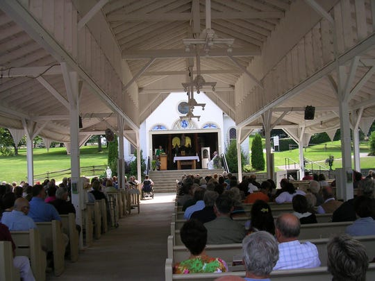 Worshippers attend a summer Mass at St. Anne's Shrine.