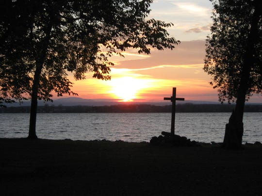 The sun sets over the Adirondacks as seen from St. Anne's Shrine.