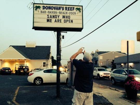 A passerby takes a picture of the Donovan's Reef sign on Saturday, July 11.