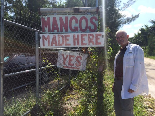 Owner Doug Flowerree stands next to the sign his father, Jack, created when he opened The Mango Factory on Bokeelia in 1980.