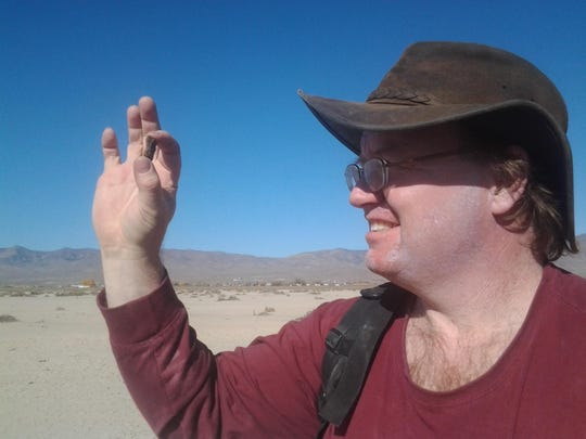 Scott Harlan of Salinas holds up a meteorite he found at Misfit Flats, southeast of Reno in Nevada. He made 19 trips to this dry lake bed and found 59 meteorites.