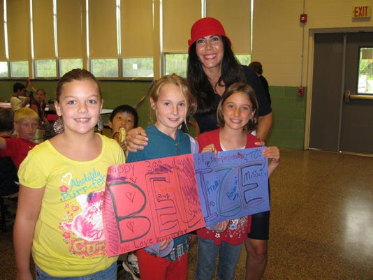 Northern Elementary Principal Joyce Cal, right, poses with students Alexa Smith, left, Shea Paxton and Raina Diziki. Cal, a native of Belize, organized a celebration of the country's independence day.