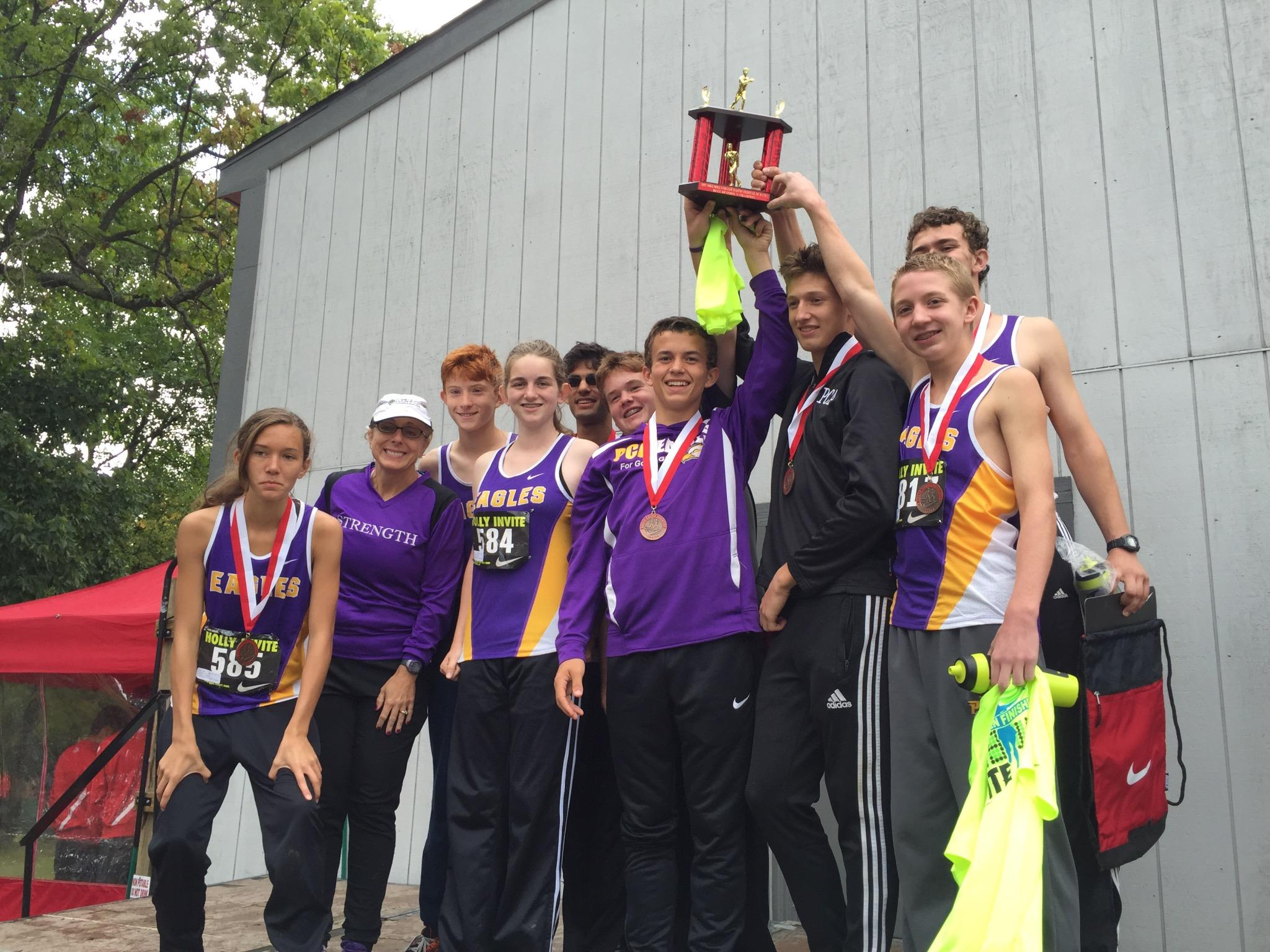 Plymouth Christian's cross country team and head coach Jennifer Lemieux celebrate winning the Nike/Holly invite.