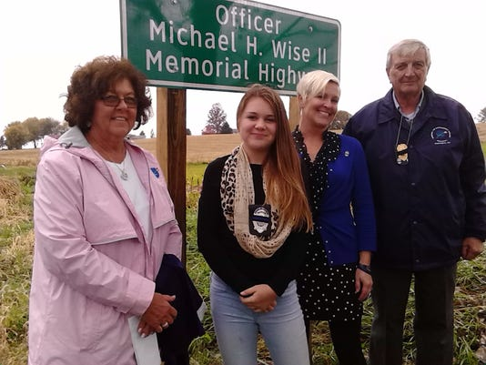 Pictured in front of the Officer Michael H. Wise II Memorial Highway sign Thursday are, from left, Wise s mother, Karen Wise; daughter Kendall Wise, wife Denise, and father Michael Wise.