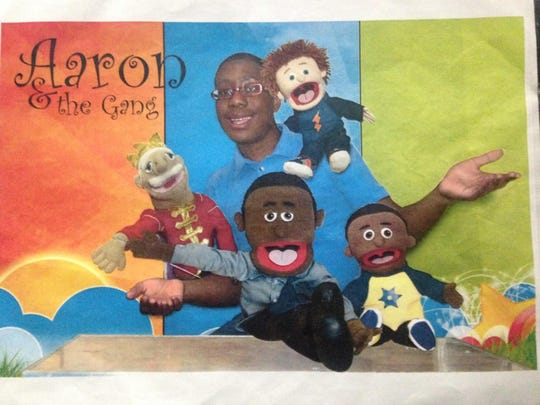 Senior Aaron Hightower plays with puppets as he practices