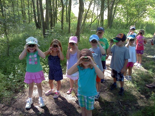This 2013 photo provided by courtesy of Ladew Topiary Gardens shows Ladew nature campers in binoculars bird watching in Monkton, Md. In this age of screens and busy schedules, nature day camps are in high demand, and many offer a more diverse array of experiences than many parents realize. (Ladew Topiary Gardens via AP)