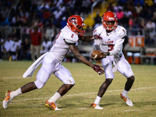 Leon's quarterback Tyhran Glasco makes a handoff to James Peterson. Behind quarterback Chris Brimm's three-touchdown night, Lincoln defeated Leon 26-3 on Friday, Oct. 14, 2016, to win a District 1-7A title and deliver the Lions a 19th straight loss.