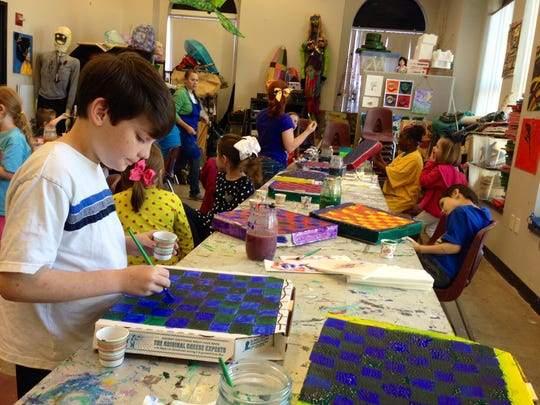 Karl Dixon, 9, turns a pizza box into a blue and green checkerboard at a holiday art camp at the Alexandria Museum of Art on Monday. Karl is a fourth-grader at Cherokee Elementary. The two-day camp allows students to create games for the holiday break out of found and recycled items.