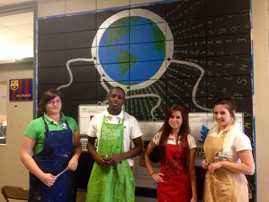 Rapides High art students are working in groups to paint seven murals across the campus. Teresa Rubio (left), La'Darius Malone, Charli Stanley and Hannah Guillory painted a globe connected to computers featuring four social media sites they use on a daily basis.