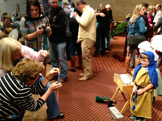 Vicki David (left, stripes) and Amy Babin take a picture of Jude Babin (right), 4, who played a shepherd in a Christmas program at Our Lady of Prompt Succor School on Tuesday.