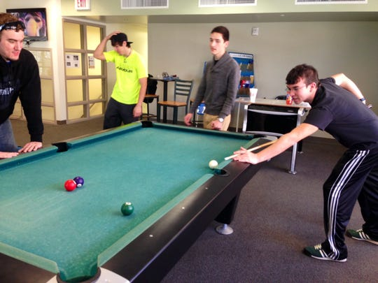 Marksville High senior Bryce Turnage (right) shoots pool at a game room in the student union between classes at Louisiana State University of Alexandria on Monday. Turnage is dually enrolled in high school and college, taking English, math, history and biology courses at LSUA this semester. The university has almost 400 dually enrolled students this spring.