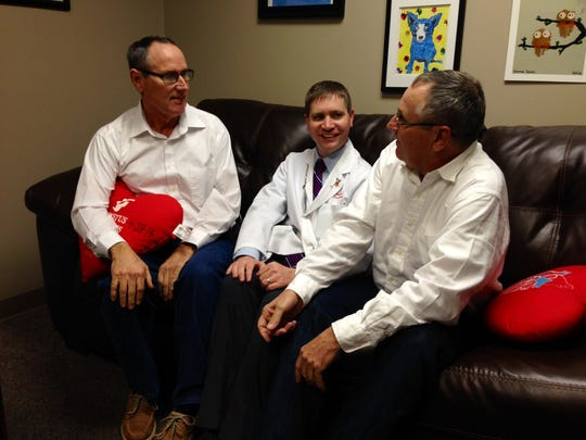 Twins Dennis (left) and Daniel Decuir (right) of Marksville talk with cardiologist Dr. Michael Smith (center), who discovered the twins both had coronary artery disease. Each brother had quadruple bypass surgery last year.