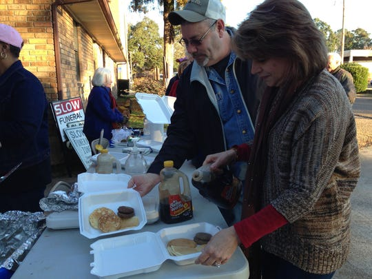 Cindy Jamison (right), secretary/treasurer for the Grant Parish Police Jury, and her husband, Johnny (left), pour syrup on pancakes they bought Friday morning at a fundraiser for a Grant Parish Sheriff's deputy.