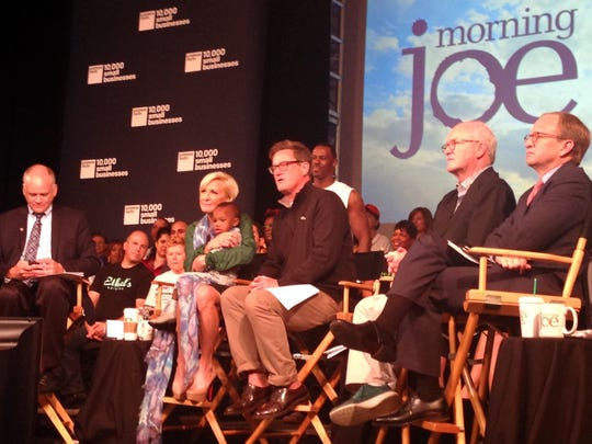 """Mika Brzezinski (holding the 18-month-old son of Steven Pierce, a 10,000 Small Businesses program graduate) and Joe Scarborough on the set of Thursday morning's live broadcast of """"Morning Joe"""" from Wayne State University."""