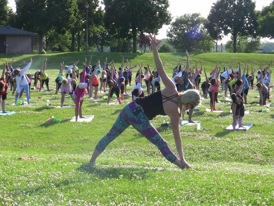 Instructor Ryanne Cunningham leads a free yoga class Thursday at Voyageur Park off of Cass St. in De Pere. Yoga in the Park is open to all skill levels and will takes place every Thursday at 6 p.m. through August.