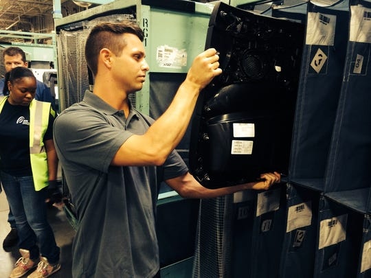 Kyle Glover shelves a X3 door panel at the Draxlmaier Group plant in Duncan