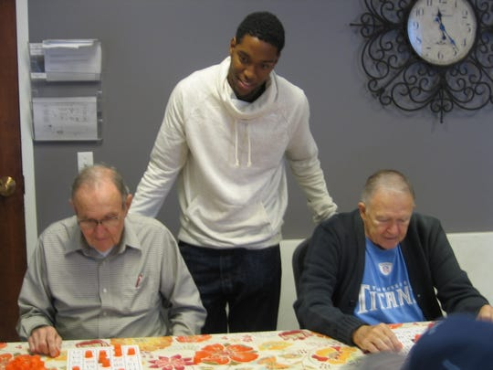 MTSU student Qua Macon assists Mindful Care participants Melvin Weber, left, and David Dean, as they peruse their Bingo cards for a number just announced. MTSU students majoring in Leisure Sport and Tourism Studies in the Department of Health and Human Performance recently visited the Mindful Care Adult Day Services program to play games and have lunch with the participants and staff.