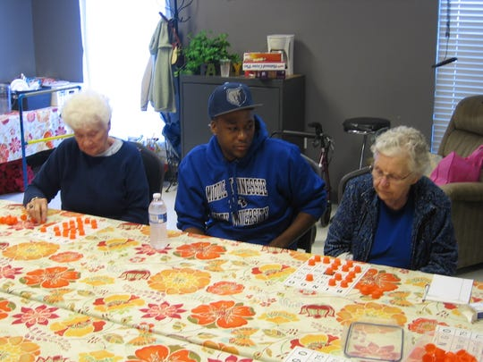 MTSU student Keyshawn Summers is flanked by Mindful Care participants Melva Reed, left, and Lorraine Pulcastro, who are intently focused on their Bingo cards. MTSU students majoring in Leisure Sport and Tourism Studies in the Department of Health and Human Performance recently visited the Mindful Care Adult Day Services program to play games and have lunch with the participants and staff.