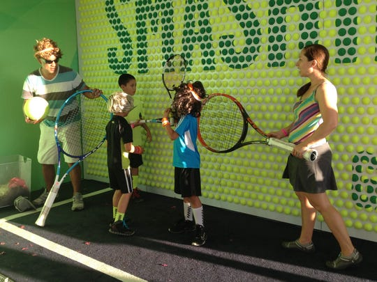 A family takes a 360 degree photo at the Bank of the West booth at Indian Wells Tennis Garden.