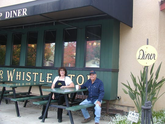 Whistle Stop owner Sherry Forcum chats with customer Tony Gonzales in the diner patio.