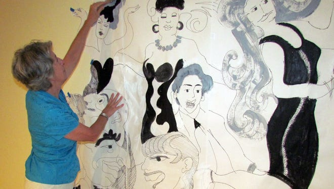 "Artist Karen Swanker works on the ""Cast of Caricatures"" mural at The Marco Players Theater. The mural is one of the theater's two new fundraisers."